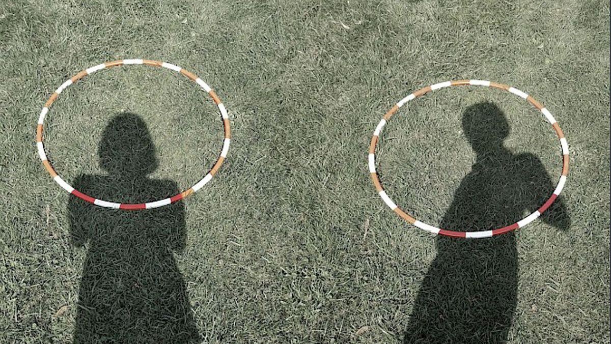 Foto von einer Performance im Englischen Garten: Menschliche Schatten und zwei gestreifte Ringe