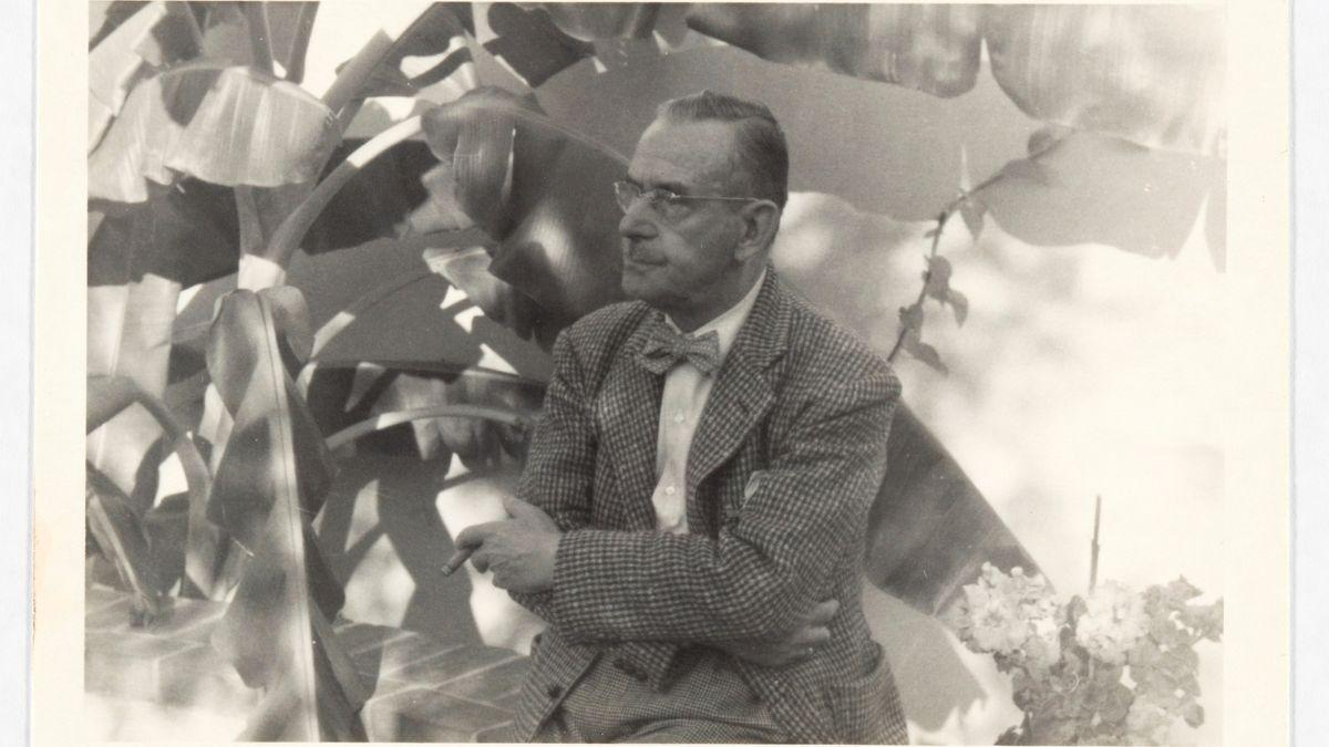 Thomas Mann sitzt um 1944 in Pacific Palisades direkt vor einer Palme, um ihn herum große Blätter. Arme verschränkt, Zigarre rauchend.