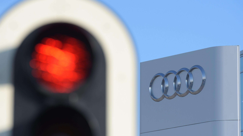 Links eine rote Ampel, rechts das Logo von Audi als Symbol dafür, dass es beim Ingolstädter Autobauer nicht rund läuft.