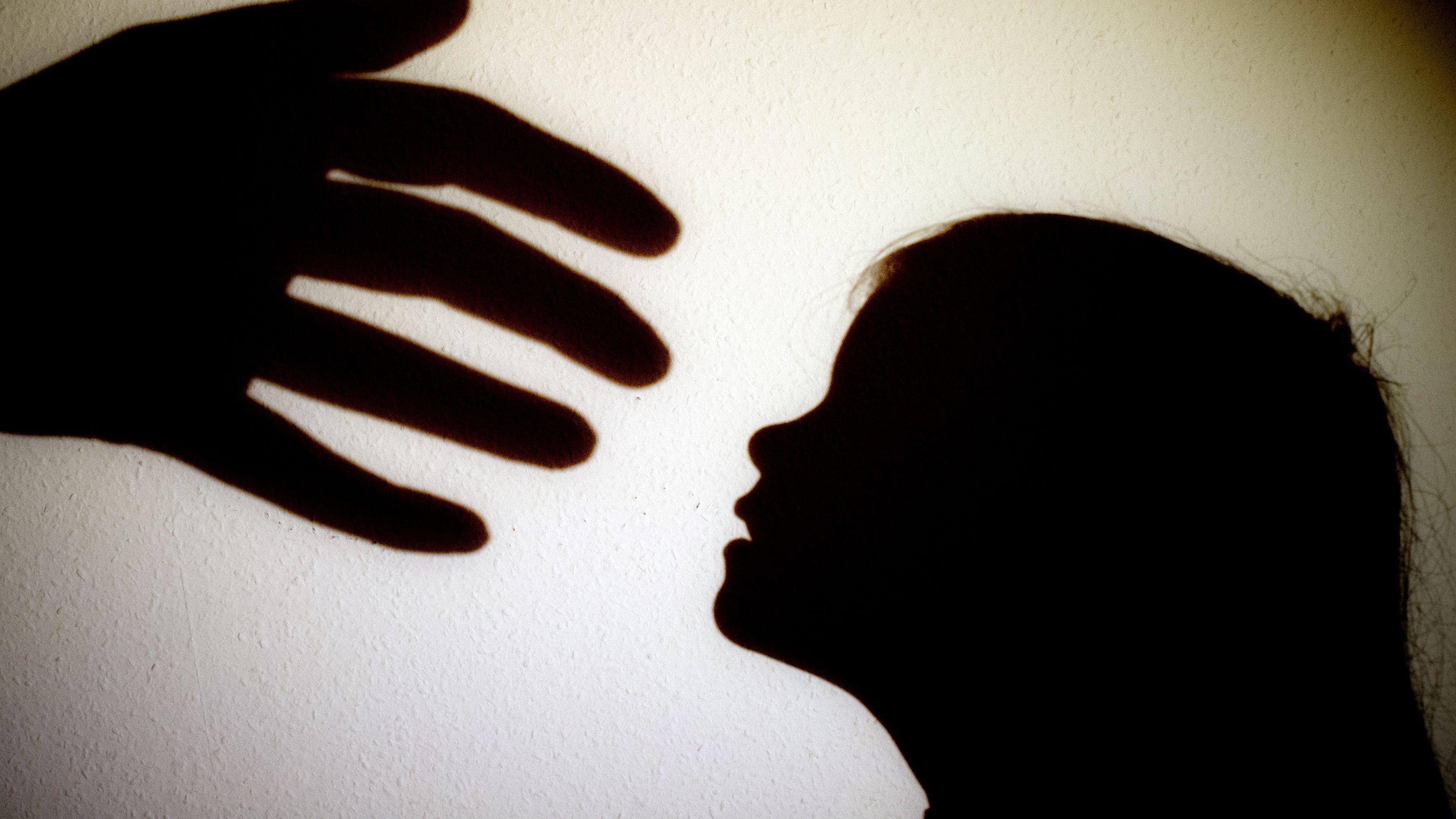 Schatten einer Hand einer erwachsenen Person und der Kopf eines Kindes