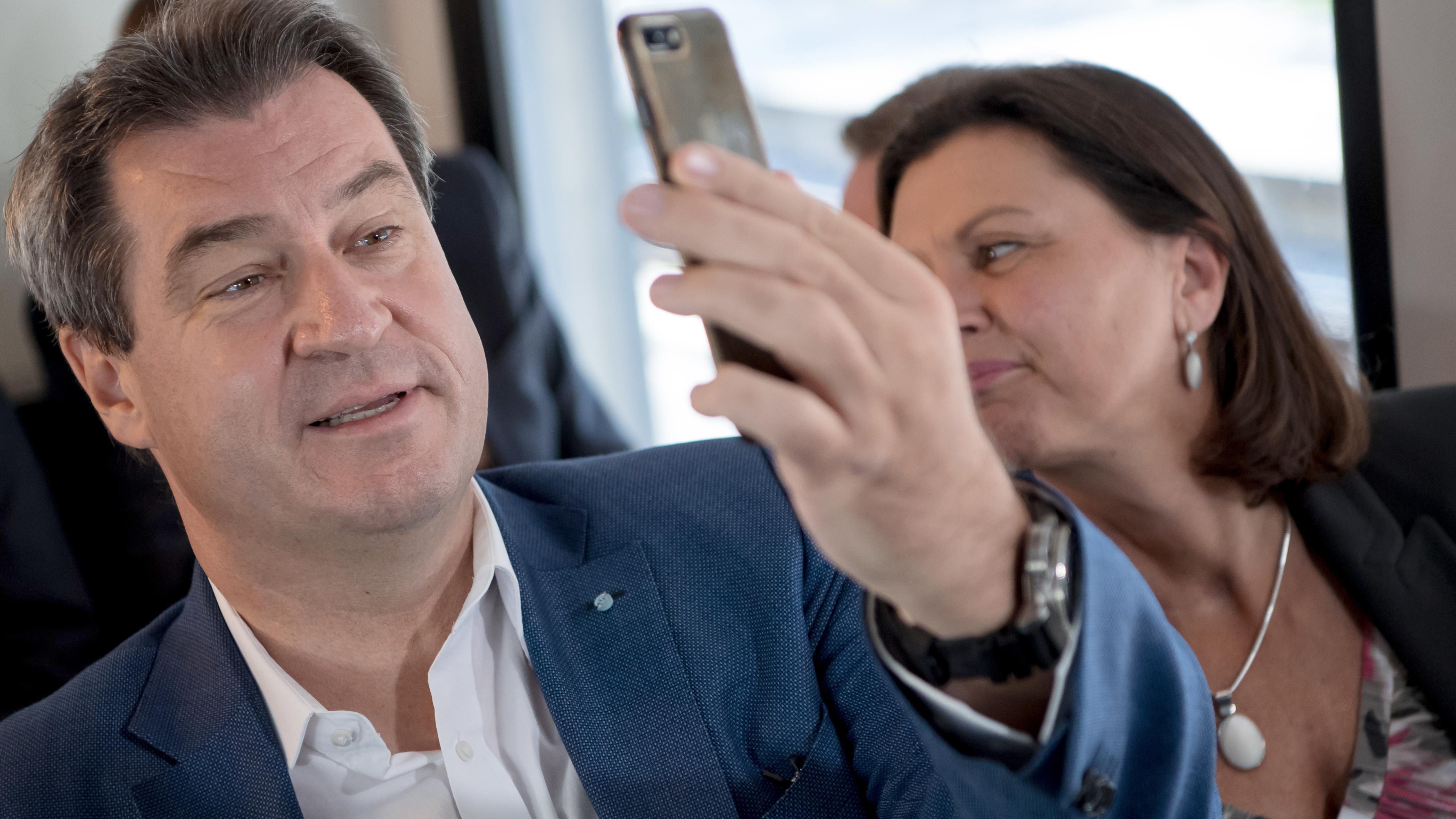Markus Söder betrachtet den Bildschirm seines Handys