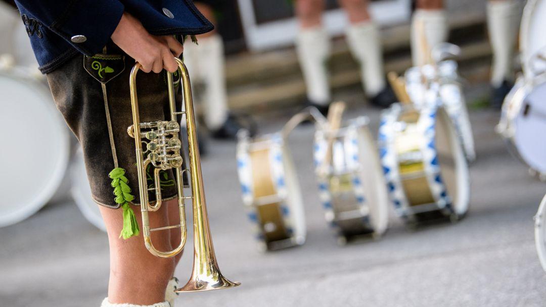 Ein Mann in Lederhose hält eine Trompete auf Hüfthöhe. Im Hintergrund sind weitere Trachtler und Trommeln zu sehen.