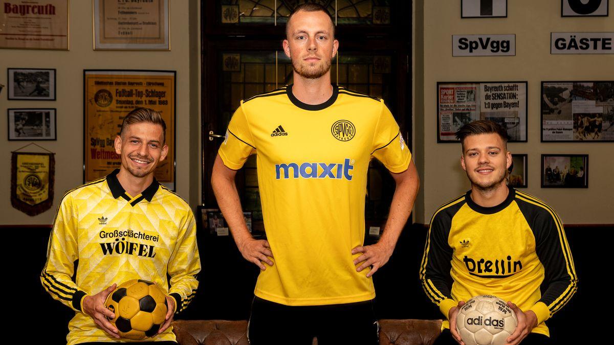 Dei Spieler der Spielvereinigung Bayreuth tragen gelbe Adidas-Trikots.