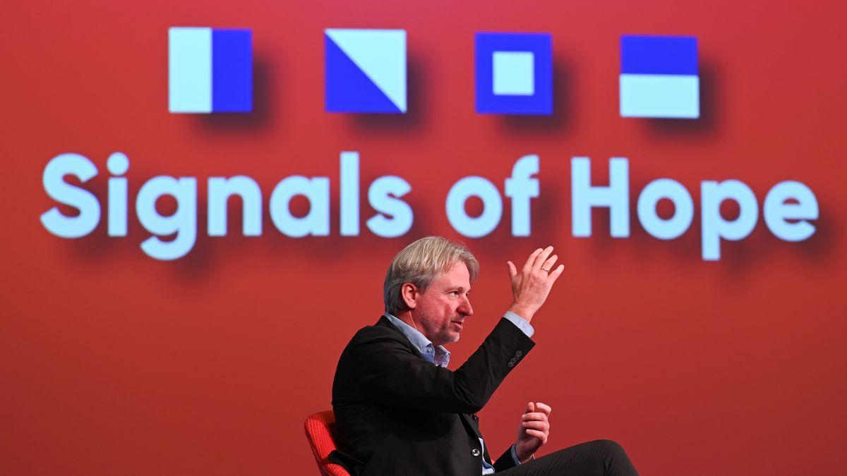 """Messechef Jürgen Boos sitzt bei der Eröffnungsfeier der Frankfurter Buchmesse vor einem roten Hintergrund mit der Aufschrift """"Signals of Hope"""""""