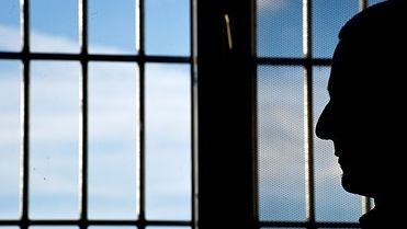 Ein Mann blickt durch ein vergittertes Gefängnisfenster.