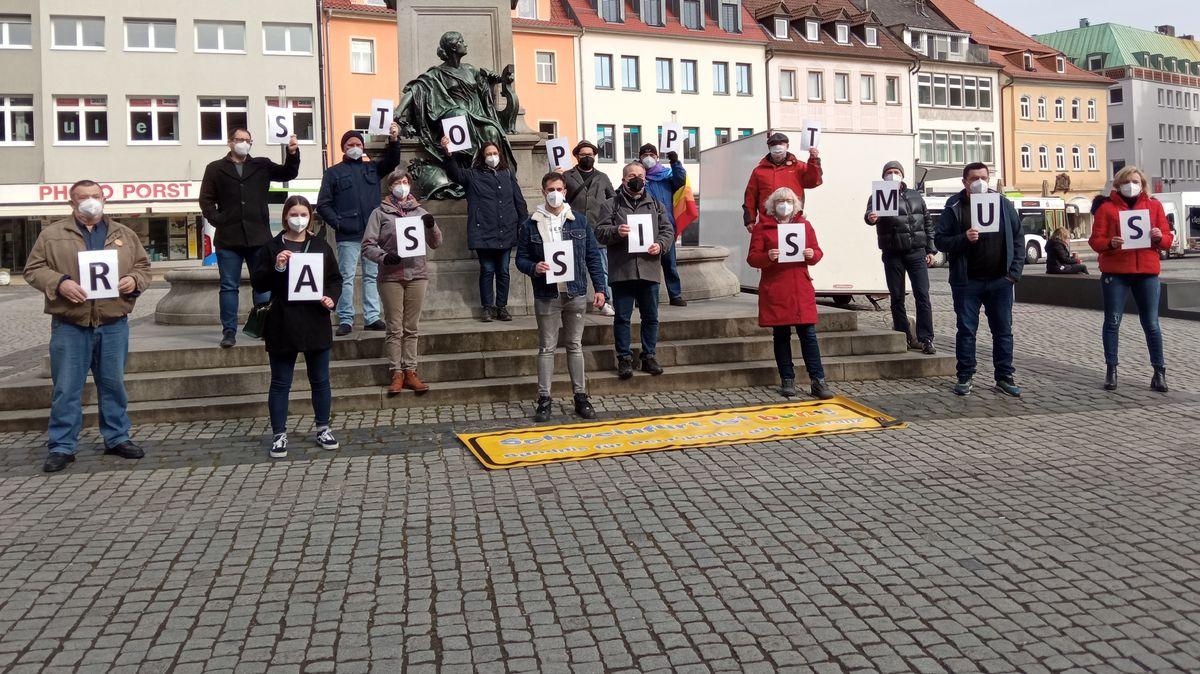 """15 Mitglieder des Bündnisses für Demokratie und Toleranz """"Schweinfurt ist bunt"""" halten auf dem Schweinfurter Marktplatz Buchstaben hoch. Diese ergeben die beiden Worte """"Stoppt Rassismus""""."""