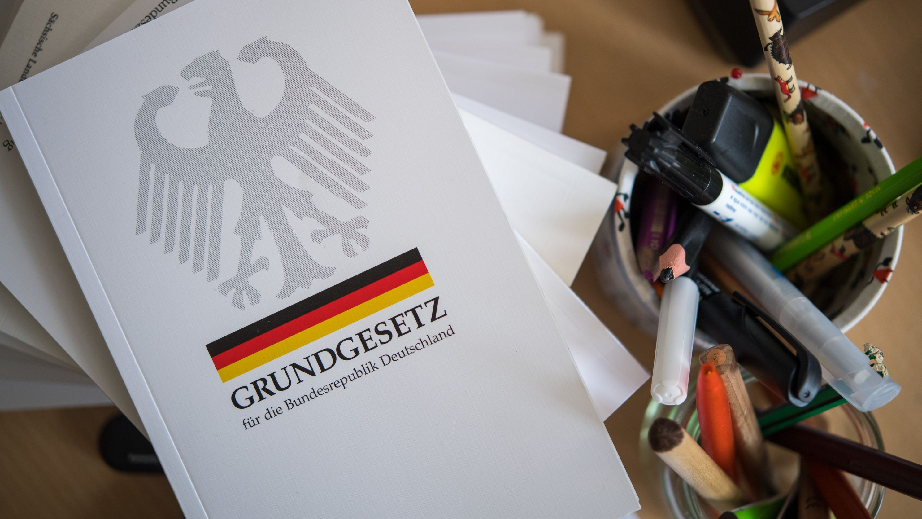 Eine Ausgabe des Grundgesetzes der Bundesrepublik Deutschland liegt auf einem Tisch neben Schreibutensilien.