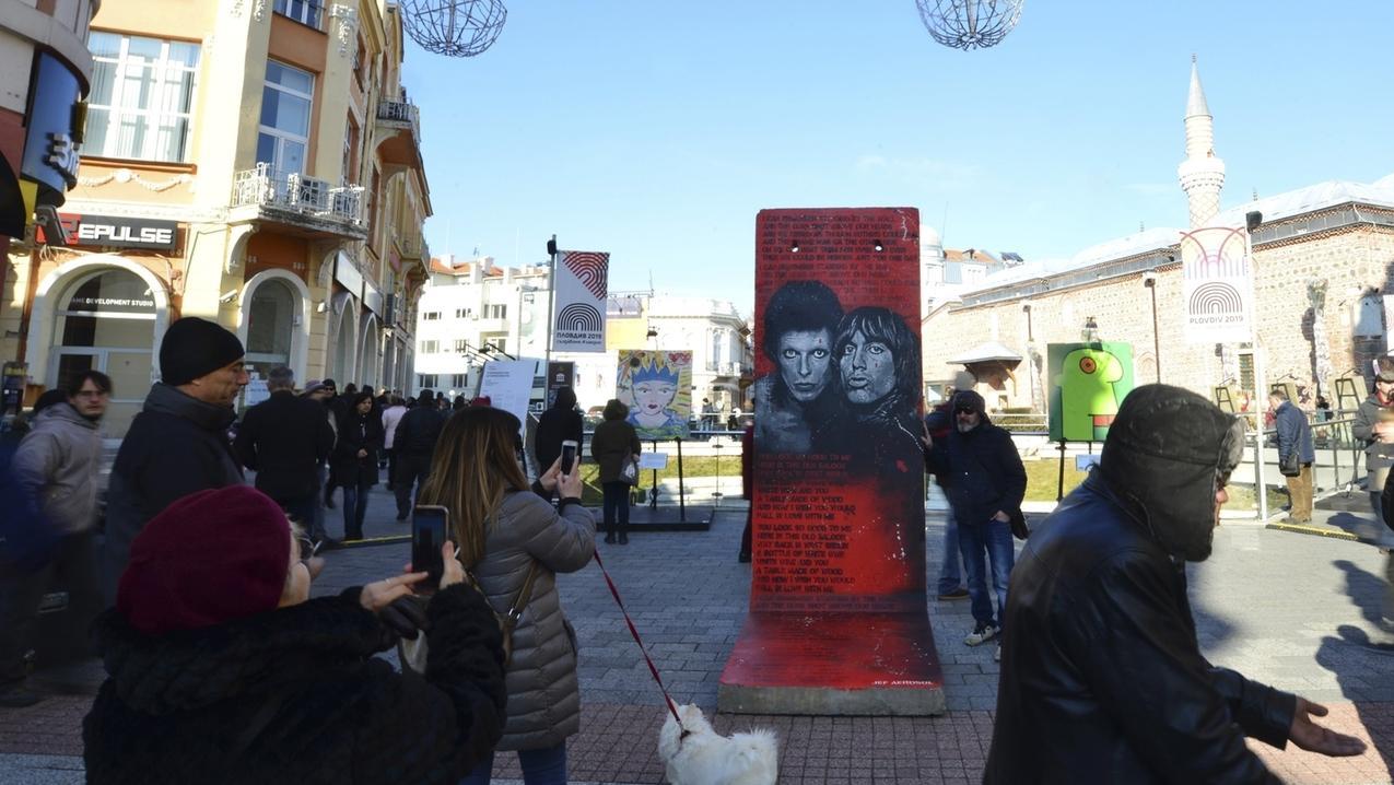 Besucher gehen vor der Eröffnungsfeier von Plowdiw als Europas Kulturhauptstadt 2019 an einem Werbeplakat für die Ausstellung Art Liberte vorbei. Die Wanderausstellung findet zum 30. Jahrestag des Mauerfalls statt.