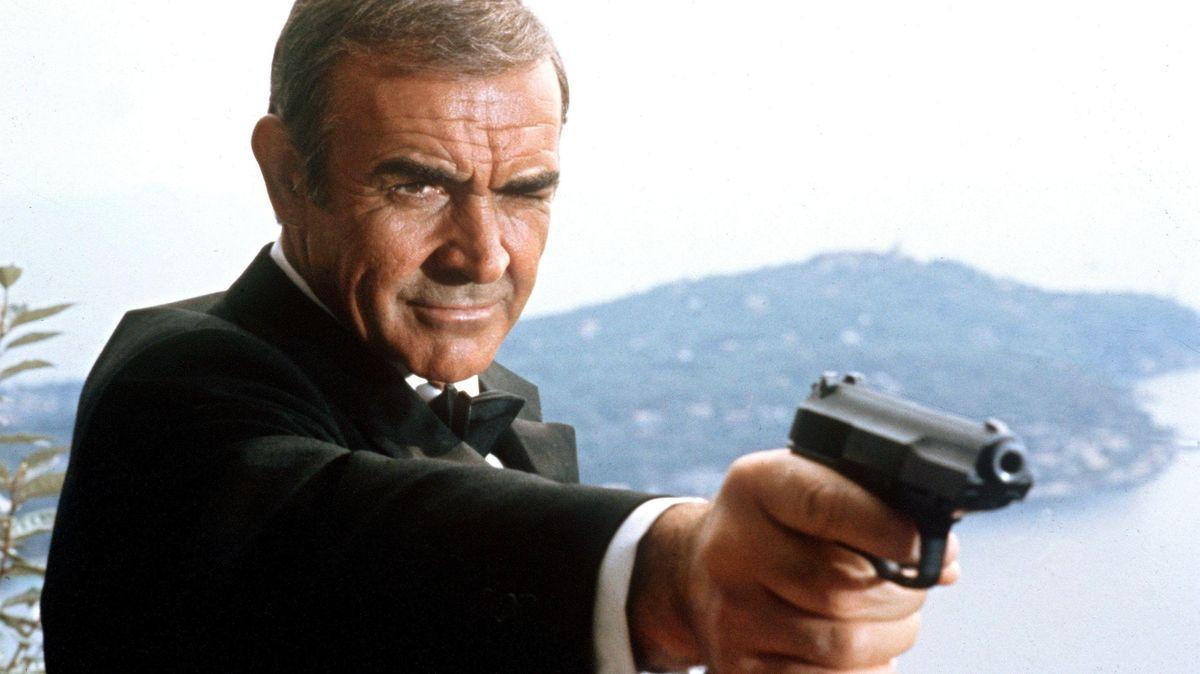 Ein Mann im Smoking zielt mit einer Pistole knapp neben den Betrachter