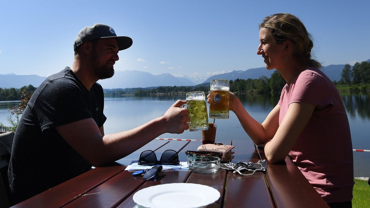 Paar stößt mit Bier am See an (Symbolbild)