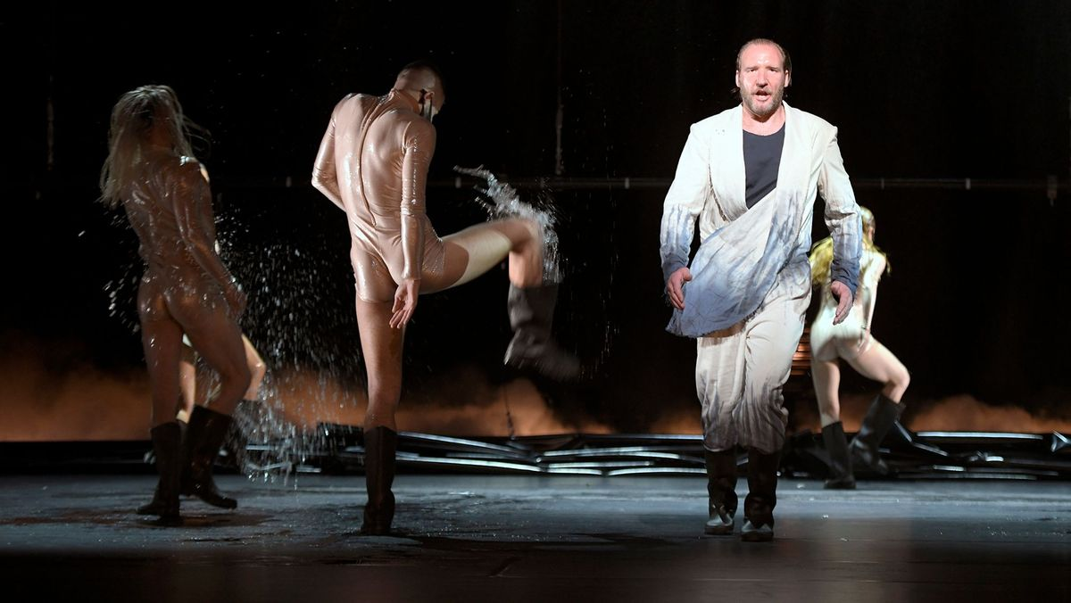 Tänzer treten im Wasser, daneben ein Sänger