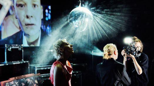 """""""Im Dickicht der Städte"""" Münchner Kammerspiele: Eine Frau filmt eine andere unter einer Diskokugel, im Hintergrund die große Projektion der Aufnahme eines Gesichts"""