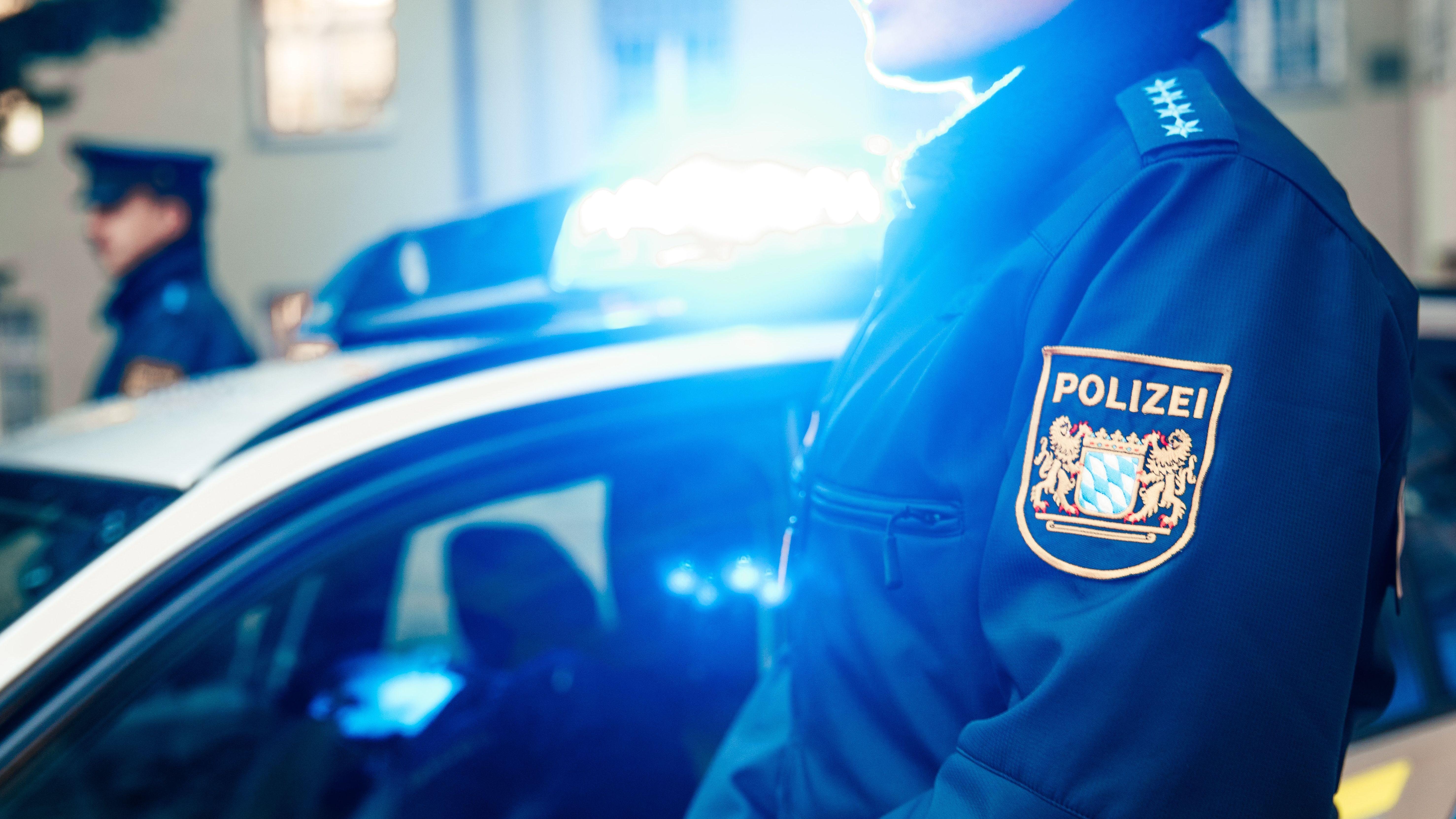 Polizeibeamter in Uniform vor Streifenwagen