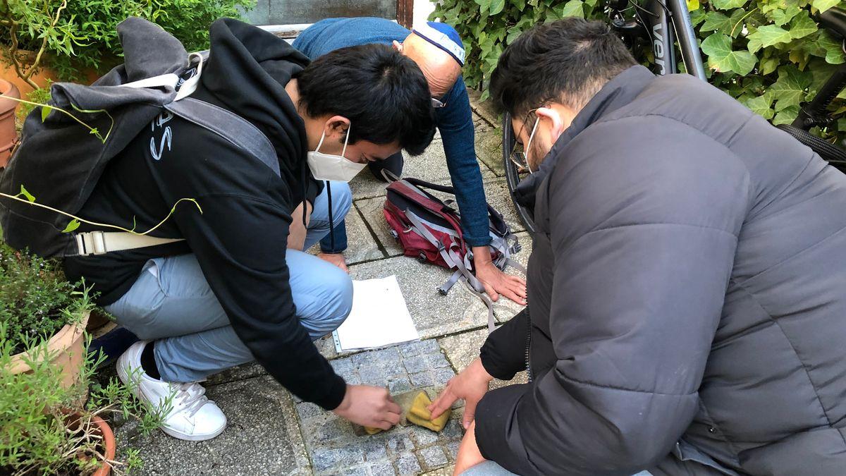 Die beiden Muslime Sayed und Waled putzen Stolpersteine, gemeinsam mit Terry Swartzberg von der Initiative Stolpersteine in München.