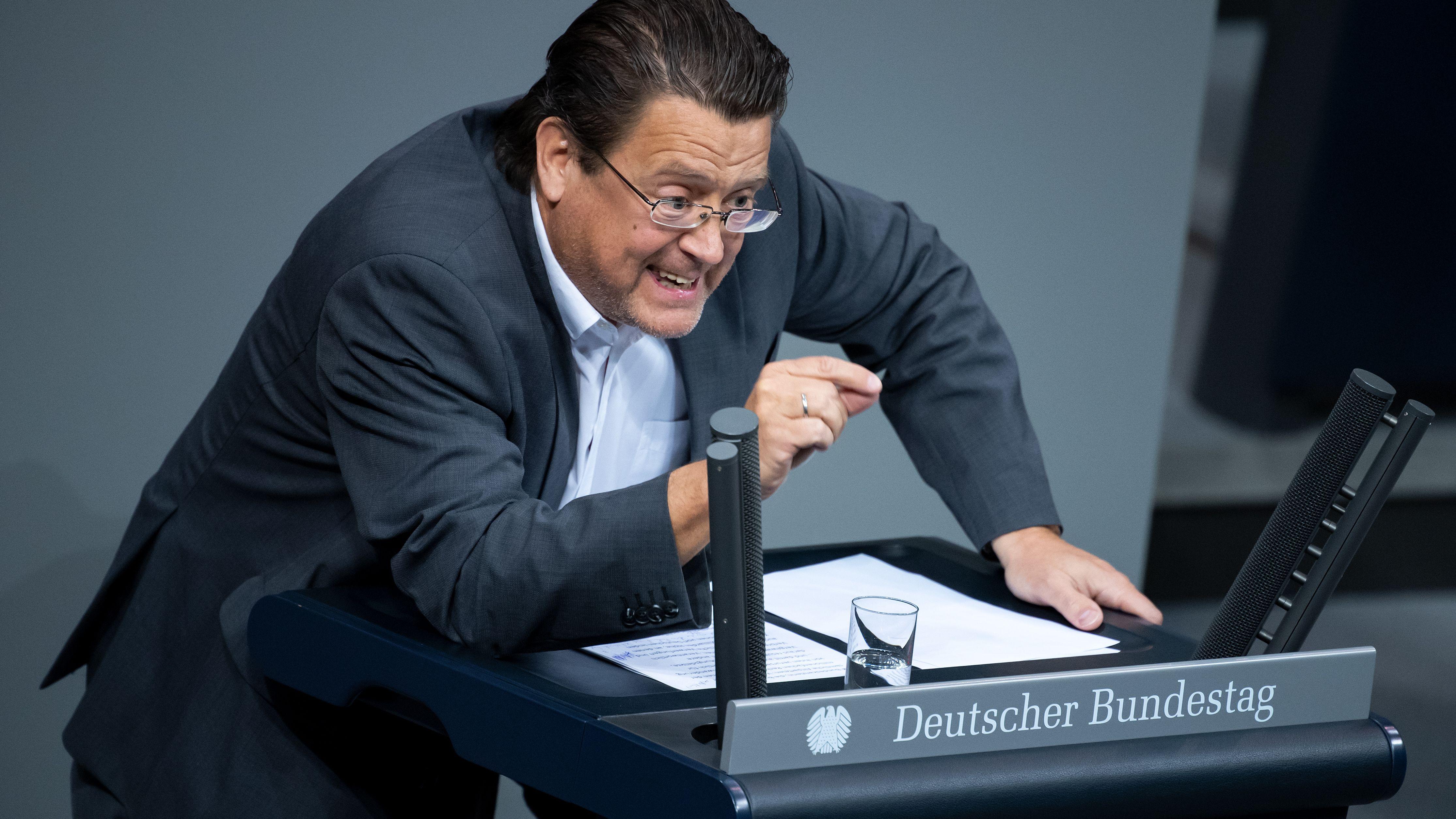 """Stephan Brandner lehnt sich an das Rednerpult mit der Aufschrift """"Deutscher Bundestag"""""""
