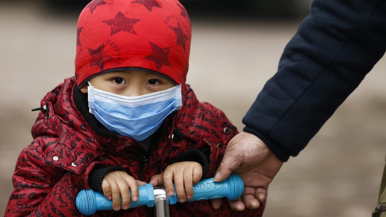 Ein Kind mit einer Schutzmaske gegen Smog fährt mit einem Roller. WHO-Bericht über die Gefahren durch Luftverschmutzung enthält neue Zahlen über durch Luftverschmutzung ausgelöste Krankheiten bei Kindern.