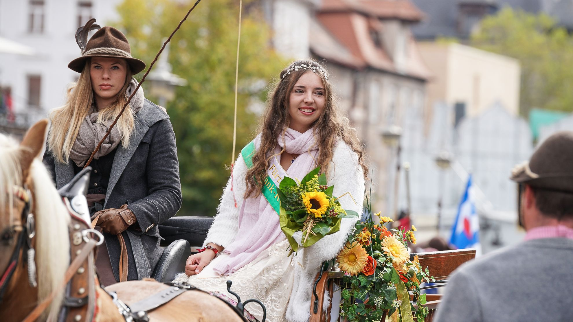 Geschmückte Frauen auf einer Kutsche