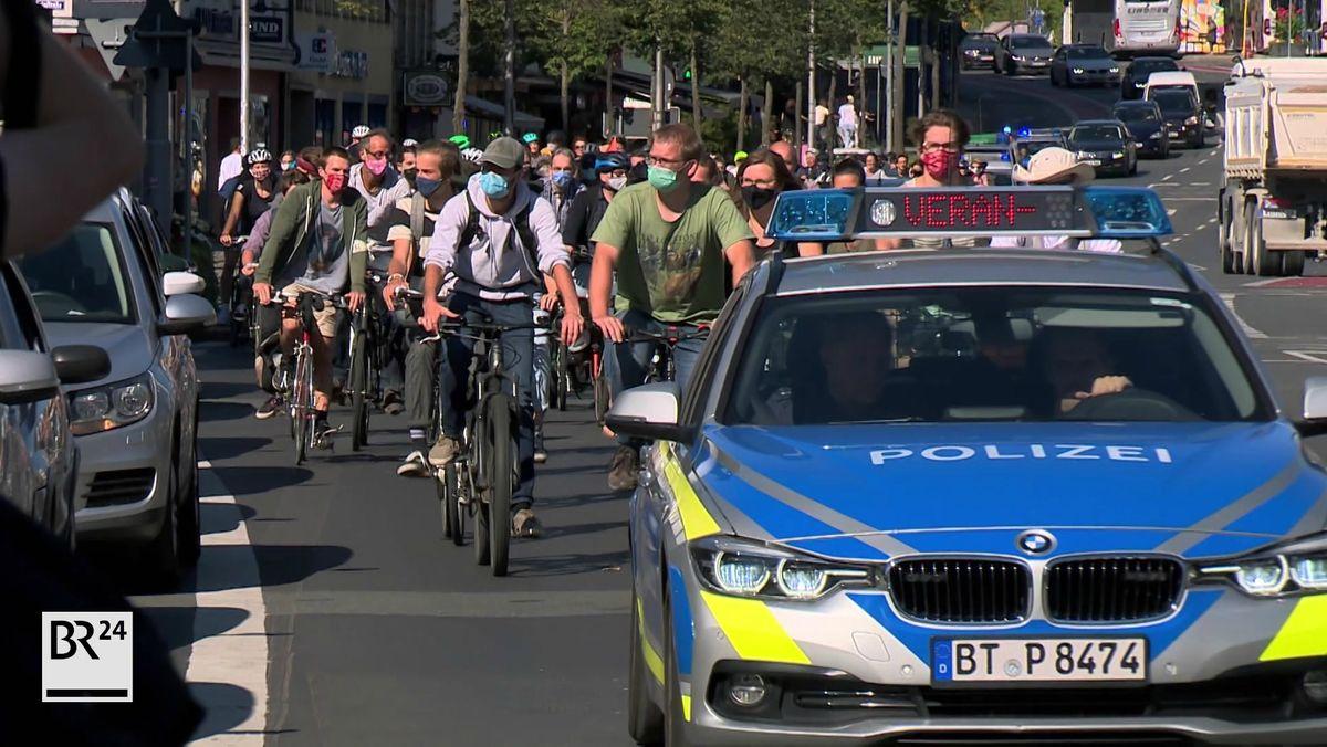 Hinter einem Polizeiauto fahren viele Fahrradfahrer mit Mund-Nasen-Schutz im Pulk durch Bayreuth.