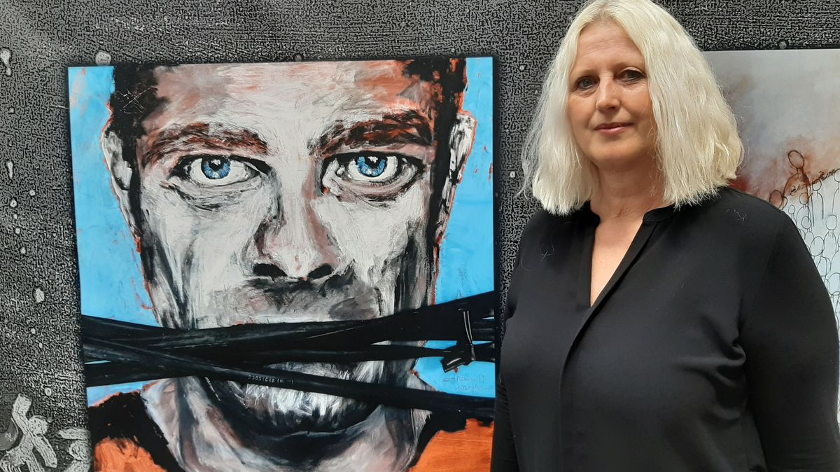 Eine Frau steht vor einem Gemälde