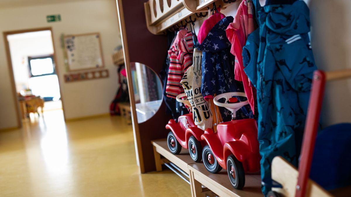 Bobbycars stehen unter Jacken von Kindern, die an einer Garderobe einer Kindertagesstätte (Kita) hängen.