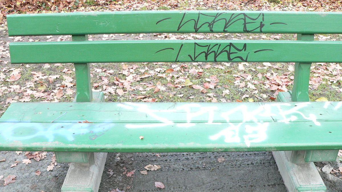 Eine grüne Parkbank, mit schwarzen und weißen Graffiti beschmiert.