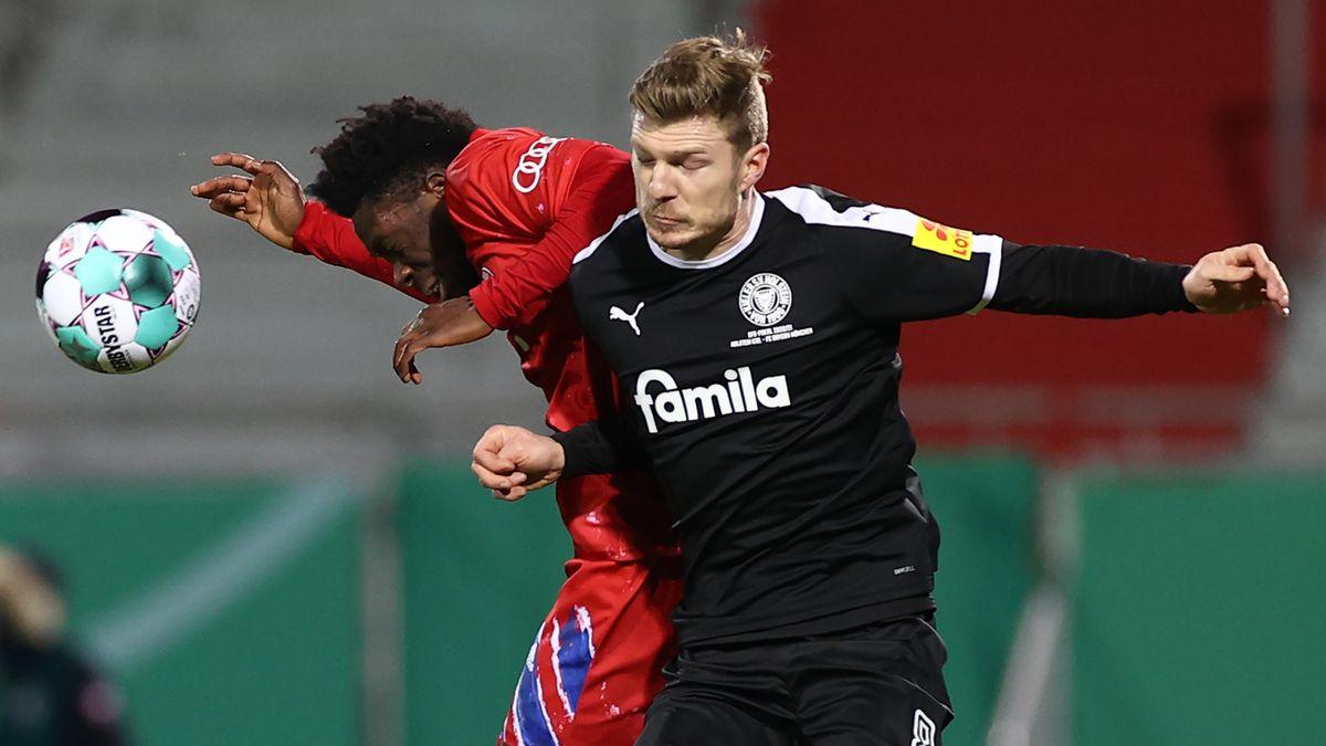 Münchens Alphonso Davies (l.) gegen Kiels Alexander Mühling