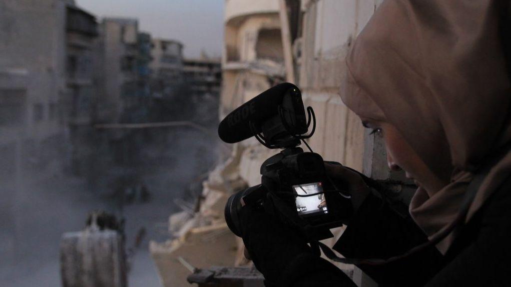 Die syrische Filmemacherin Waad al-Kateab filmt aus dem Fenster eines Hauses in Aleppo den Krieg unten auf der Straße.