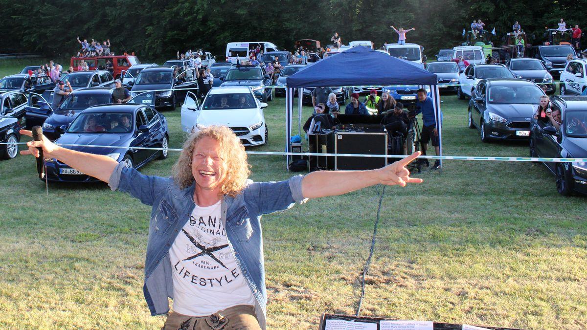 """Ein Bandmitglied der """"Troglauer Buam"""" auf der Bühne - Im Hintegrund die Konzertbesucher auf oder in ihren Autos."""