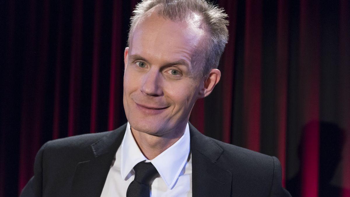Kabarettist Max Uthoff blickt lächelnd vor einem roten Bühnenvorhang in die Kamera
