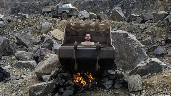 Eine Baggerschaufel mit einem halbwegs unbekleideten Mann drin zwischen großen Steinsbrocken