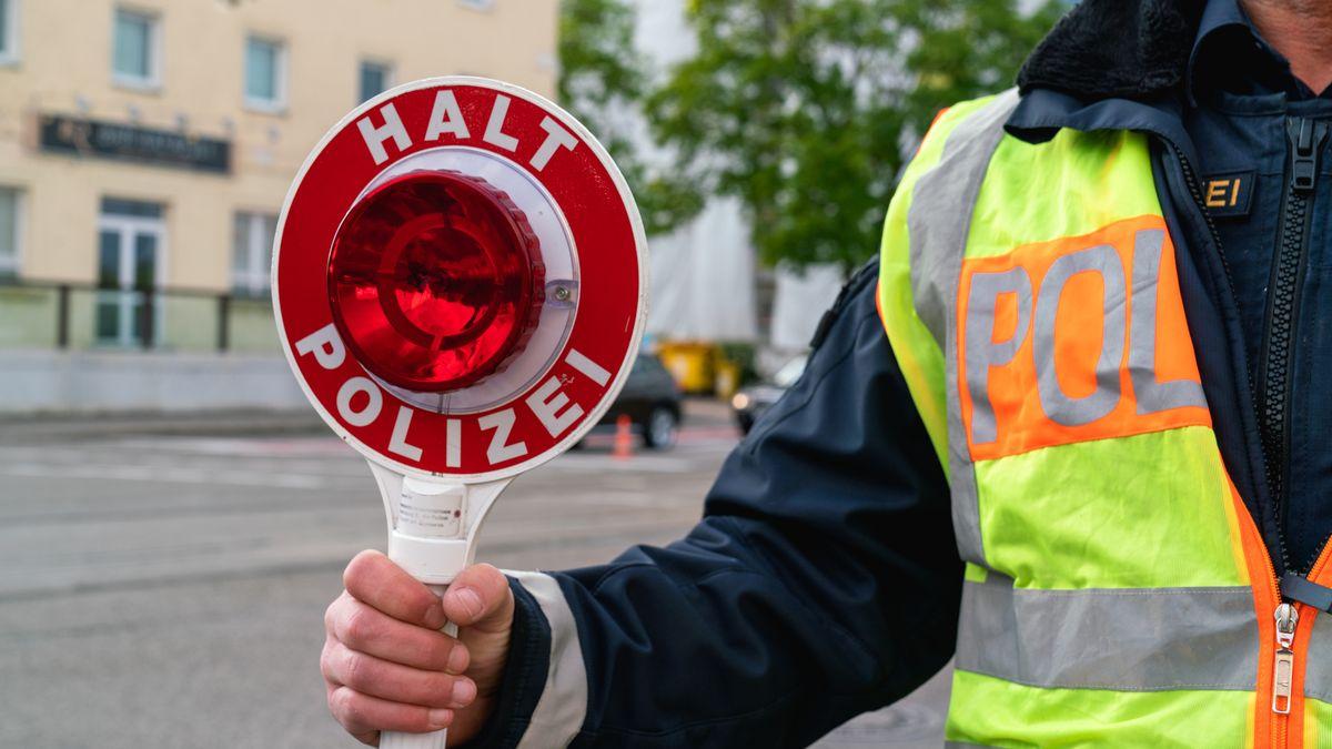 """Polizist hält mit Kelle mit der Aufschrift """"Halt Polizei"""" (Symbolbild)"""