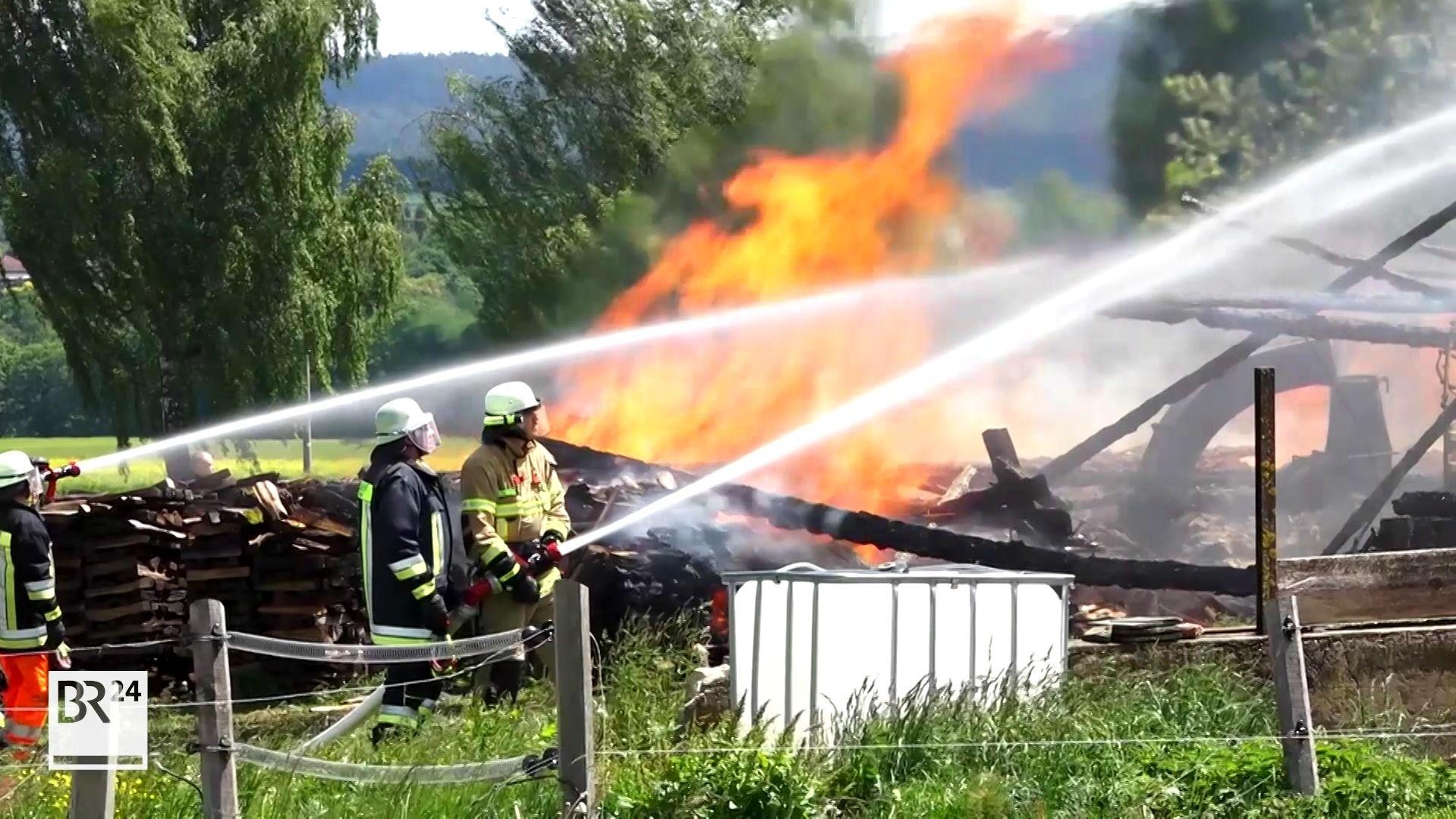 Feuerwehrmänner bei Löscharbeiten - im Hintergrund Sind Schutt und Flammen zu sehen.