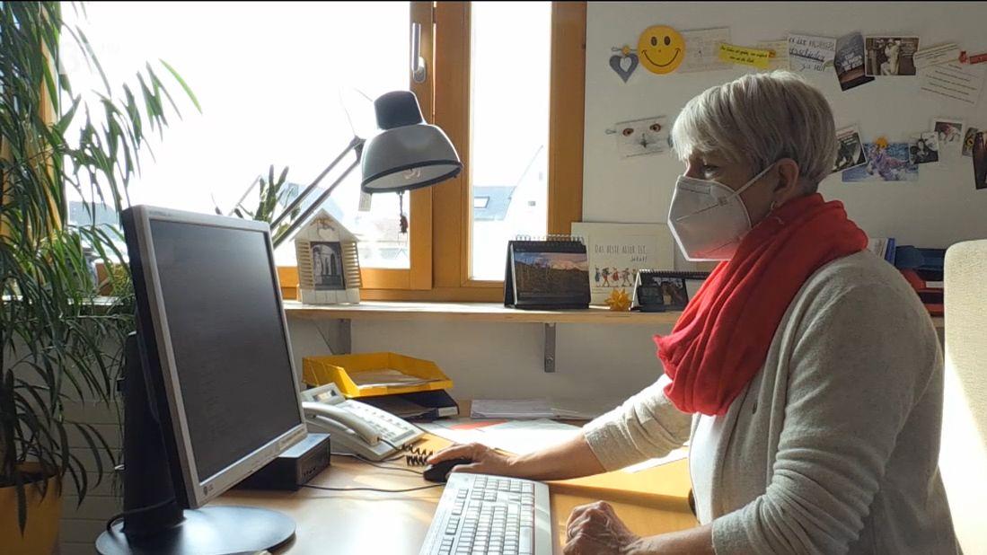 Eine Sachbearbeiterin sitzt mit FFP2-Maske an ihrem Arbeitsplatz in Ansbach
