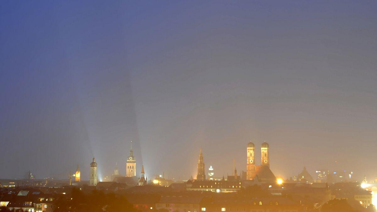 Der Nachthimmel leuchtet über der Skyline der bayerischen Landeshauptstadt München.