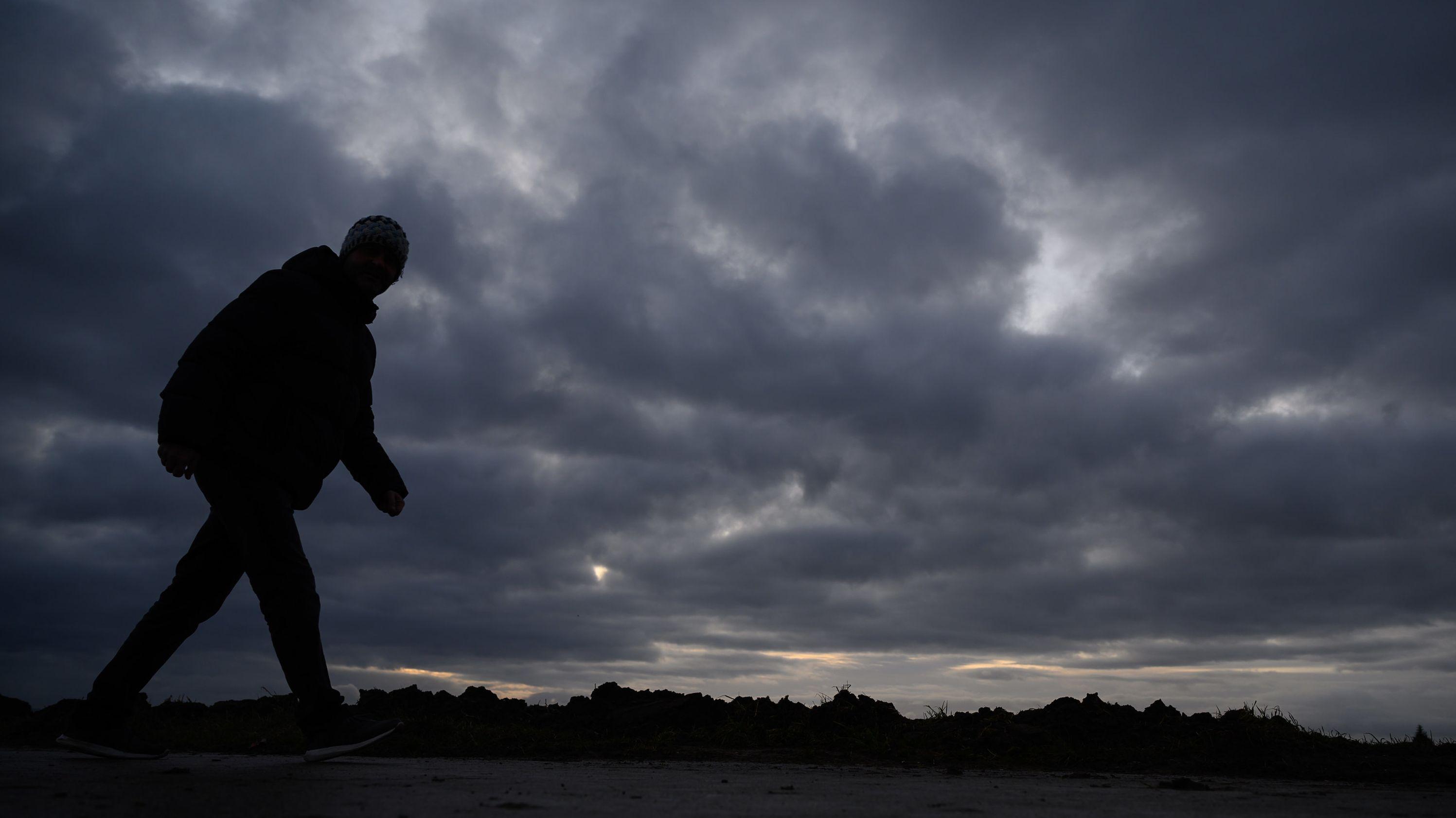 Spaziergänger vor dunklen Wolken (Symbolbild)