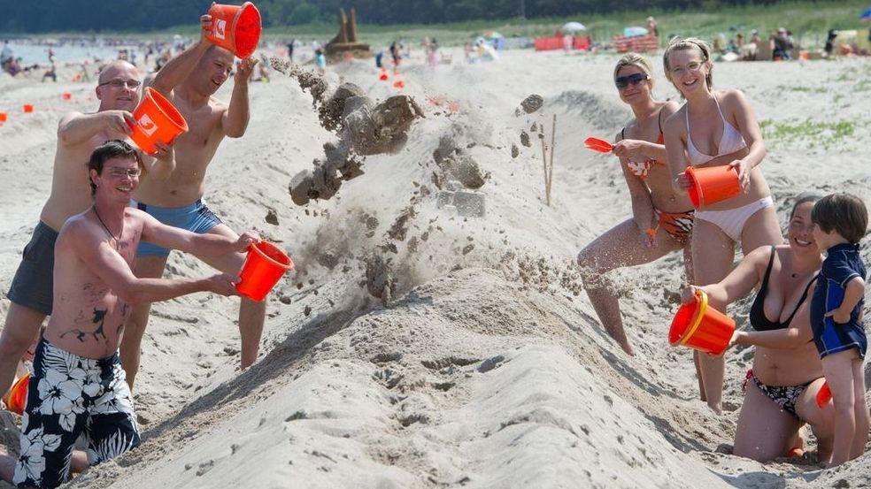 Viele Urlauber bauen an einer großen Sandburg