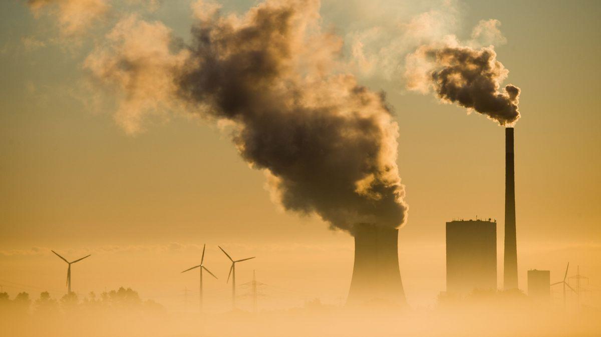 Symbolbild: Ein Kohlekraftwerk und Windräder produzieren Strom.