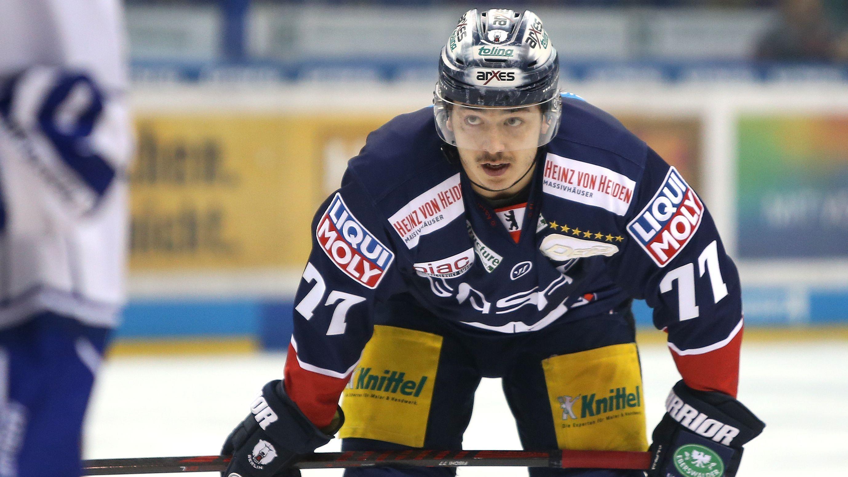 Eishockey-Spieler Daniel Fischbuch im Eishockey-Outfit mit Eishockey-Schläger.