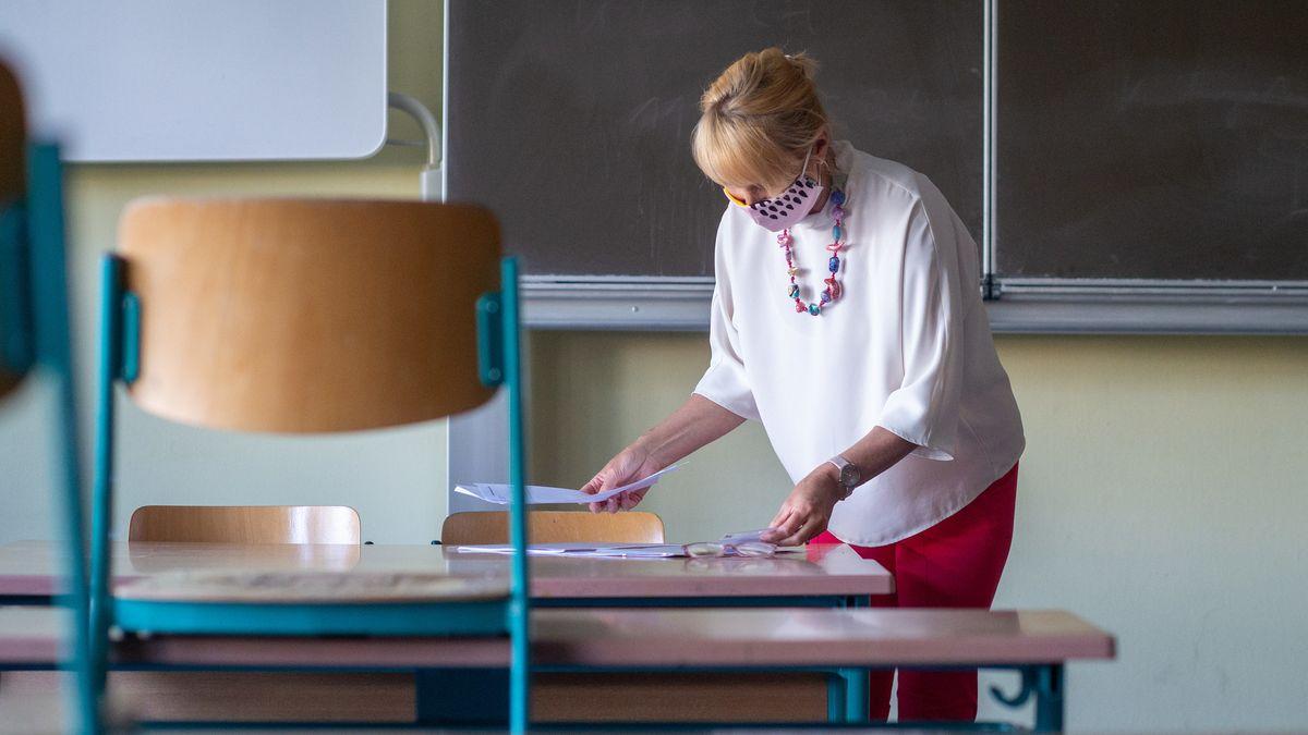 Eine Lehrerin mit Mundschutz in einem leeren Klassenzimmer