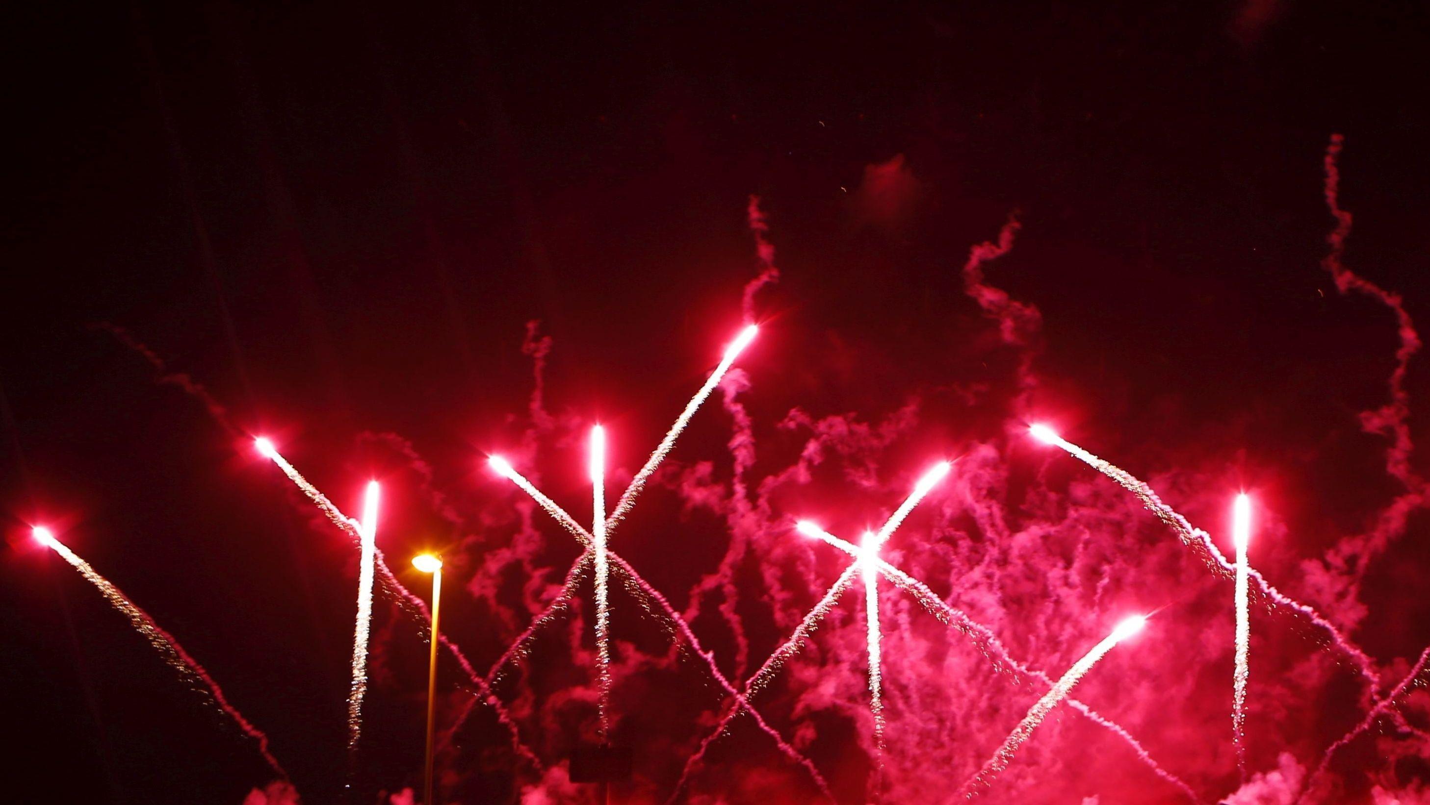 Rote Silvesterraketen schießen in den dunklen Abendhimmel