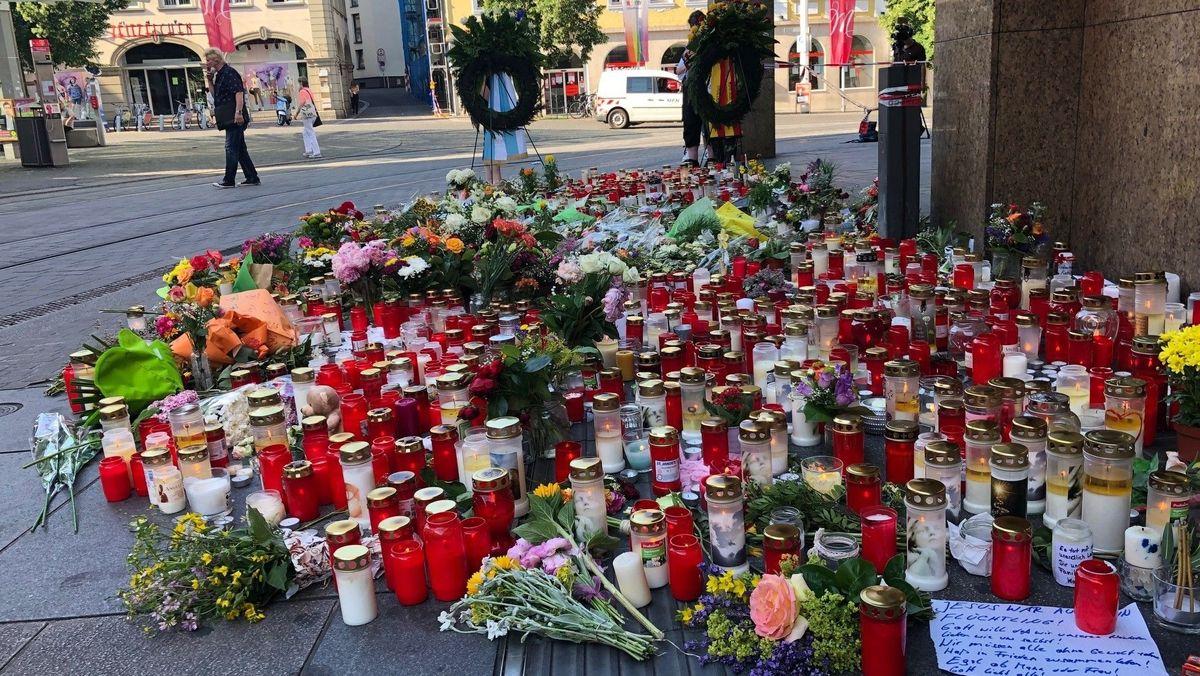 Kränze, Blumen und Kerzen am Ort der Messerattacke, einem Kaufhaus in der Würzburger Innenstadt.
