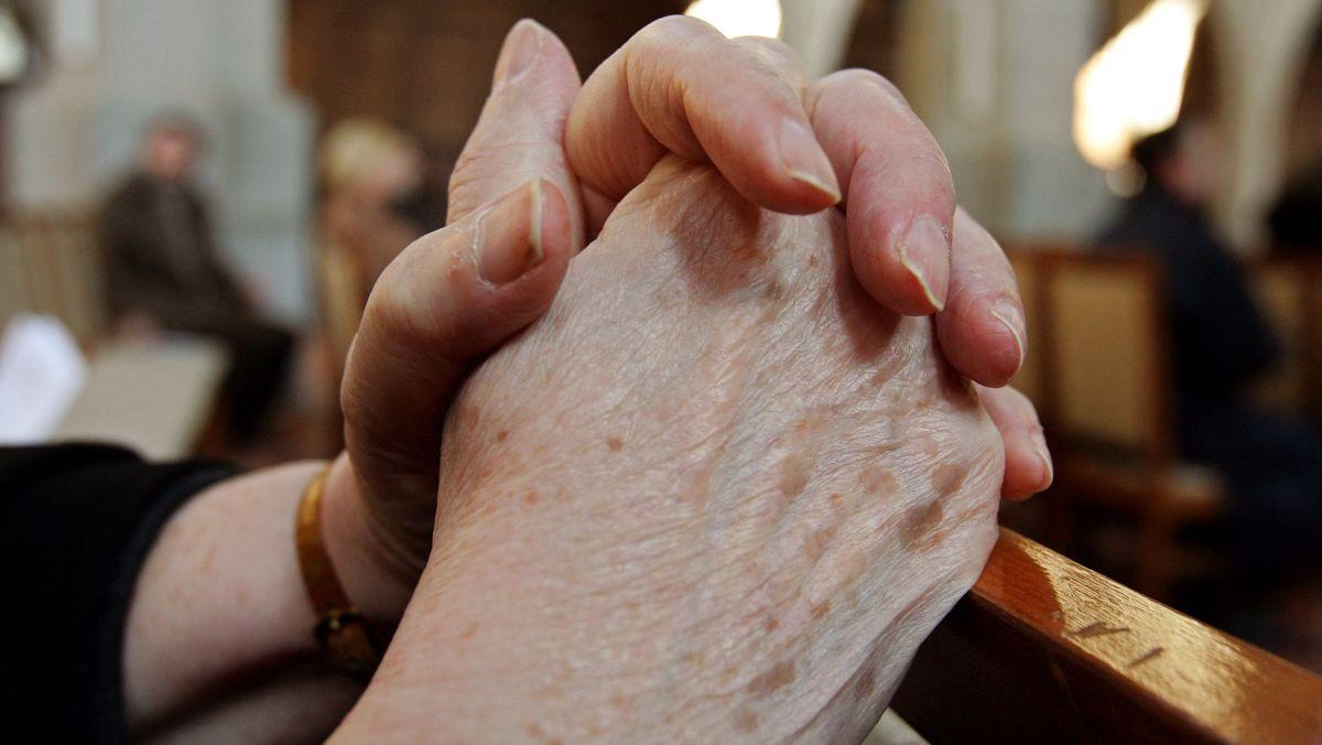 Gefaltete Hände einer alten Frau in einer Kirche