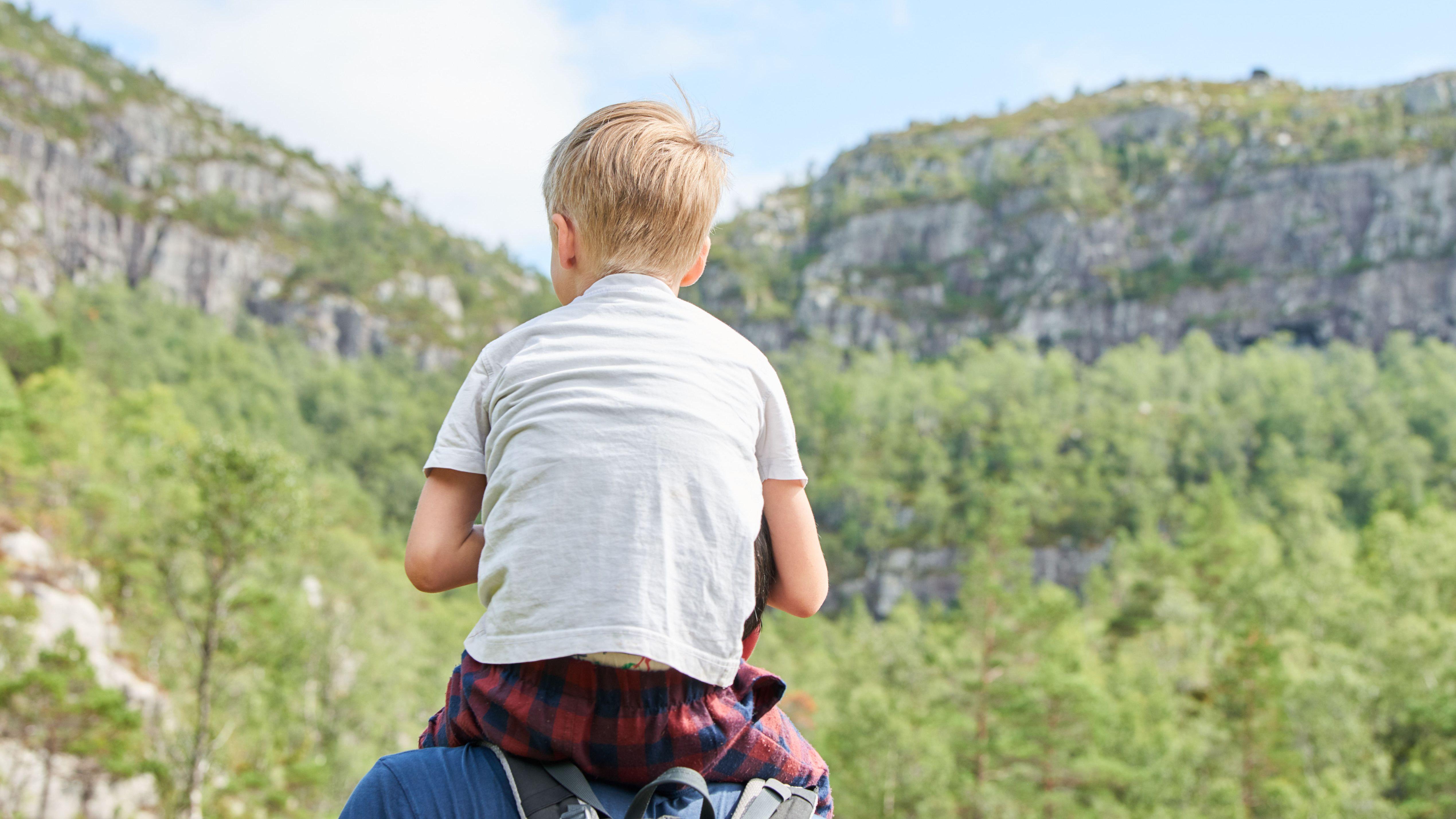Ein Junge auf den Schultern seines Vaters in einer norwegischen Landschaft.