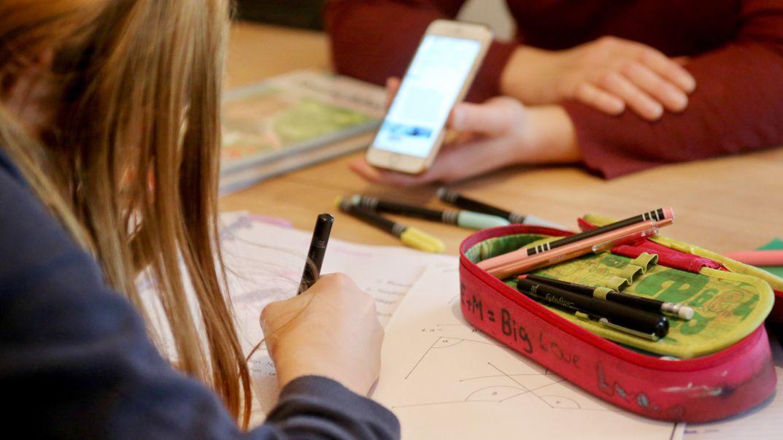 ARCHIV - 11.01.2021, Nordrhein-Westfalen, ---: Eine Mutter (r) hilft ihrer zwölfjährigen Tochter beim Homeschooling und hält ein Smartphone in der Hand.
