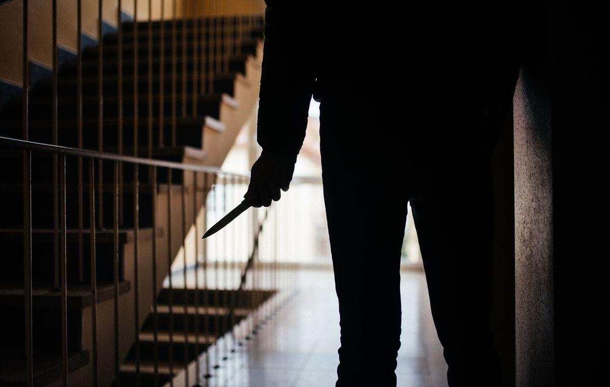 Ein Mann in einem Treppenhaus hält ein Messer in der Hand (Symbolbild)