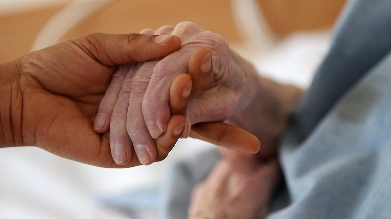 Eine Person hält die Hand eines älteren Menschen.