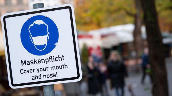 """Symbolbild: Ein Schild mit der Aufschrift """"Maskenpflicht Cover your mouth and nose!"""""""