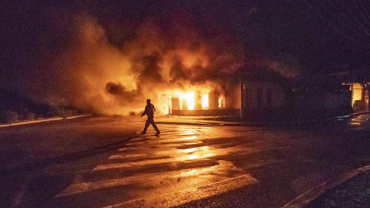 Mann vor brennendem Gebäude in Stepanakert.