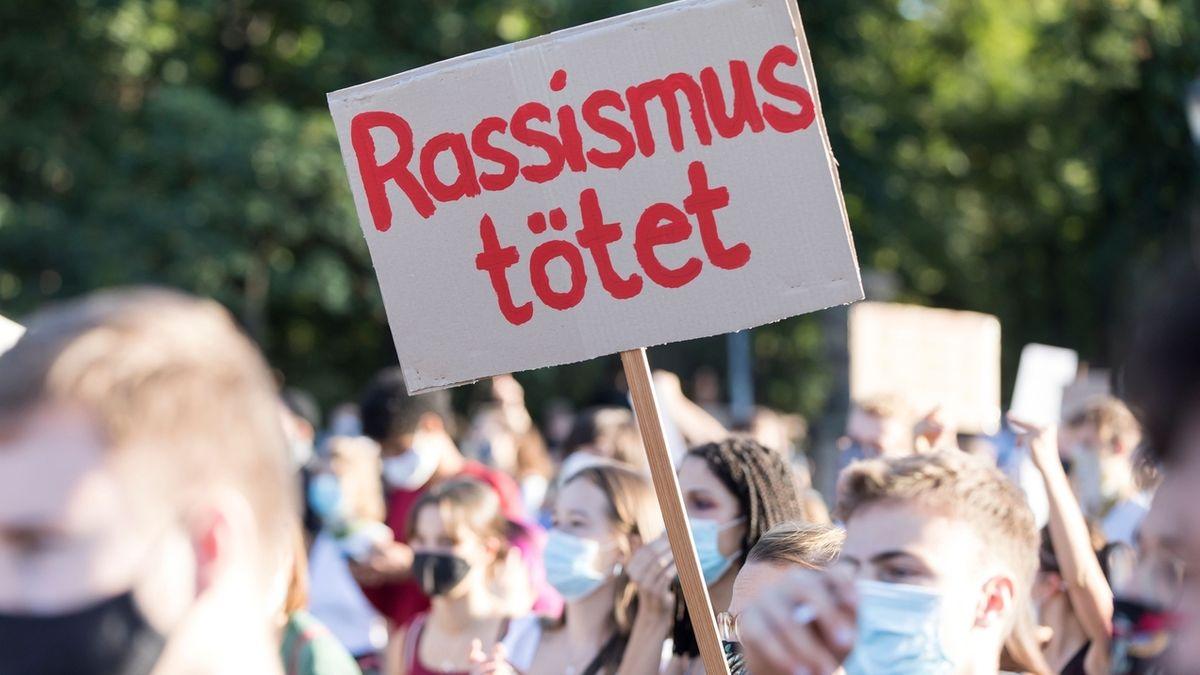 """Teilnehmer mit Schild """"Rassismus tötet"""". Für die Aufnahme von Flüchtlingen und die Räumung der Lager auf Lesbos demonstrierten am 20.09.2020 etwa 11.000 Menschen in Berlin."""