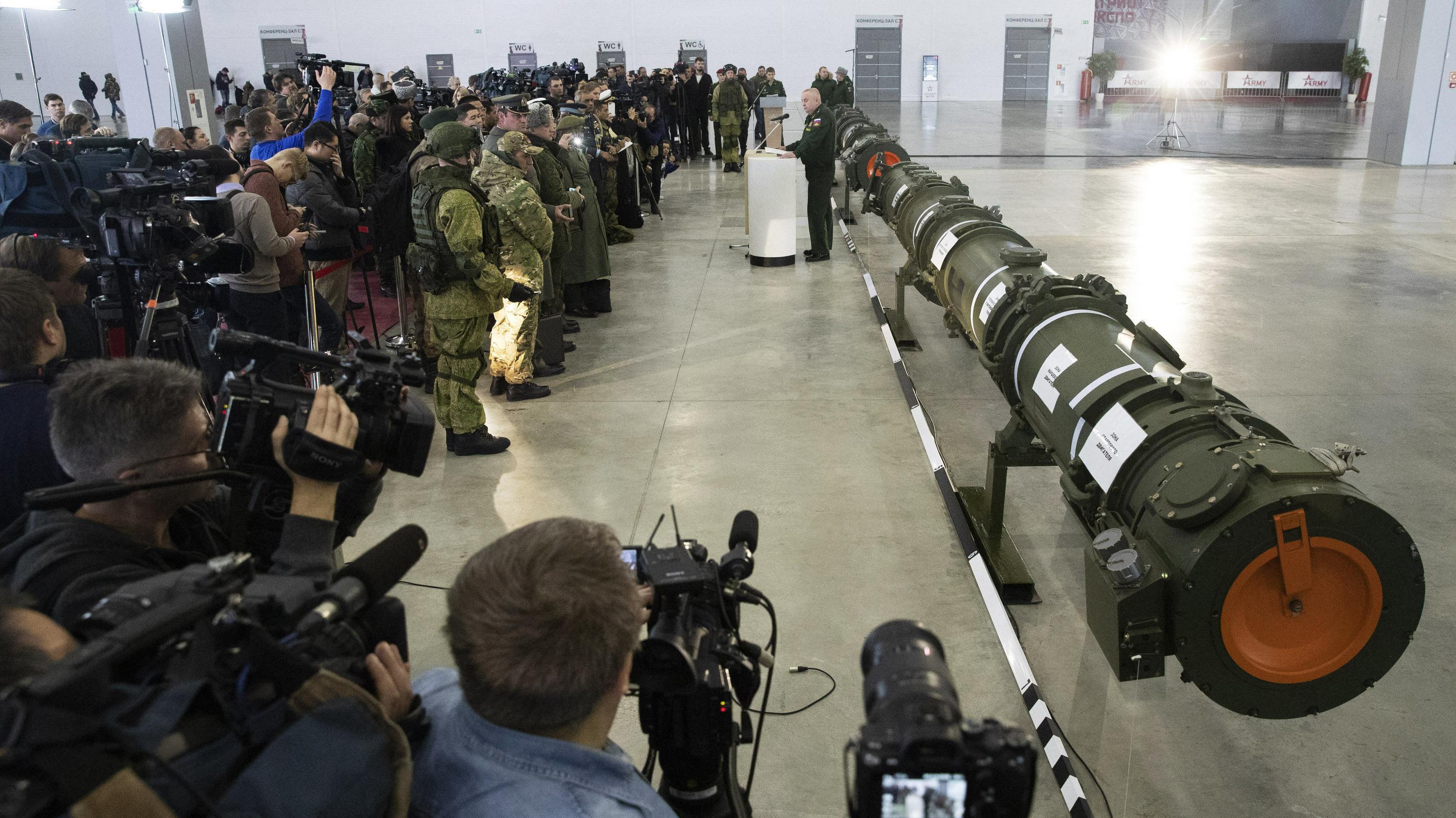 Journalisten mit Kameras und Soldaten in Uniformen stehen vor langen Behältern, die die neue Rakete enthalten